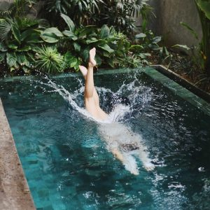 Women jumping in clear pool surrounded with plants by Taylor Simpson.